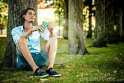Male Relaxing Under Tree Outdoors -  #adult #thoughtful #casual #young #20 #model #positive #sun #handsome #outside #telephone #park #charm #thinking #posing #attitude #communications #smile #tree #one #body #outdoor #relax #green #summer #portrait #attractive #outdoors #relaxed #under #smartphone #talk #calm #charming #happy #white #talking #grass smiling #masculine #male #relaxing #man