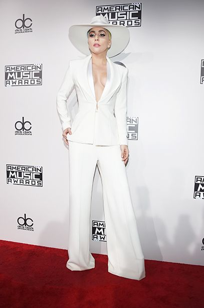 Lady Gaga was white-hot in a simple suit of wide-leg trousers and a plunging blazer, worn with a wide-brimmed hat and heels.