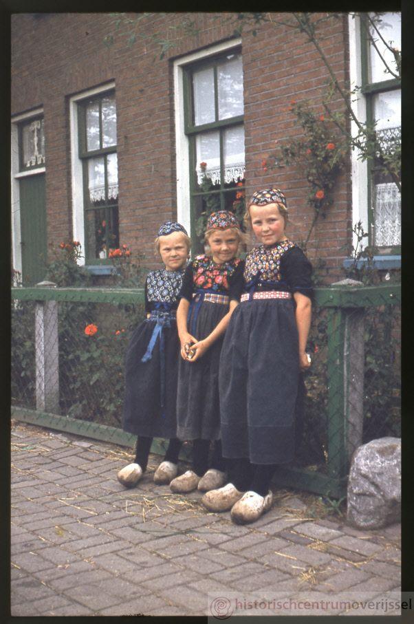 Drie meisjes in Staphorster klederdracht poseren voor de camera. 1974-1976…