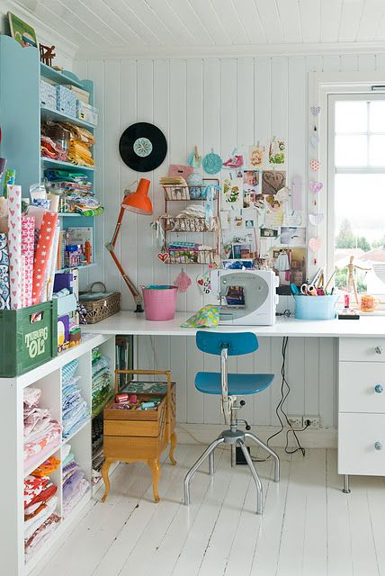 Adorable sewing space. The turquoise shelf...