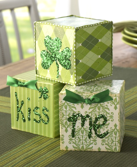 """Kiss Me Blocks created with Mod Podge and dimensional magic ~St. Patrick's Day is a great reason to get your kids crafting. ~PLAID SUPPLIES: *Mod Podge-CS11273 Gold Shimmer *CS11215 Mod Podge Dimensional Magic ~OTHER SUPPLIES: 3 ½"""" wood blocks, Green glitter, 5/8"""" Green satin ribbon, Green and white damask paper, Green pinstripe paper, Green argyle paper, Scissors, Hot glue"""