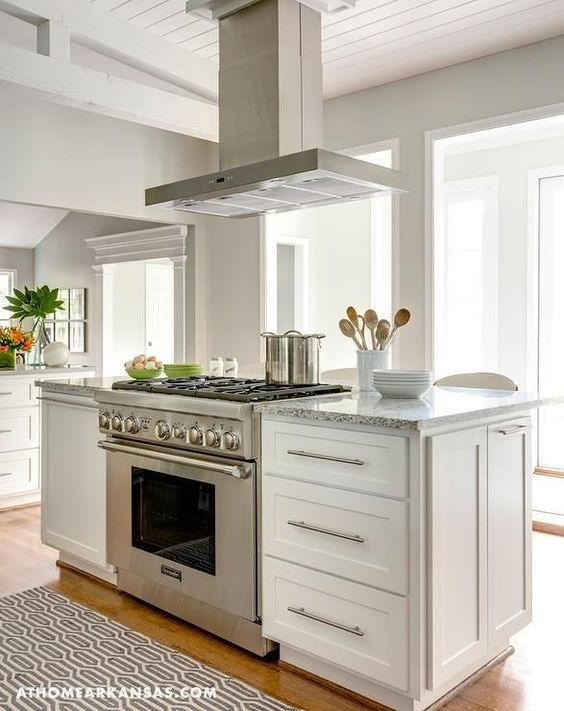 A stainless steel kitchen hood stands over a kitchen island fitted with white cabinets and a gray granite countertop as well as a stainless steel freestanding stove alongside a gray trellis rug.