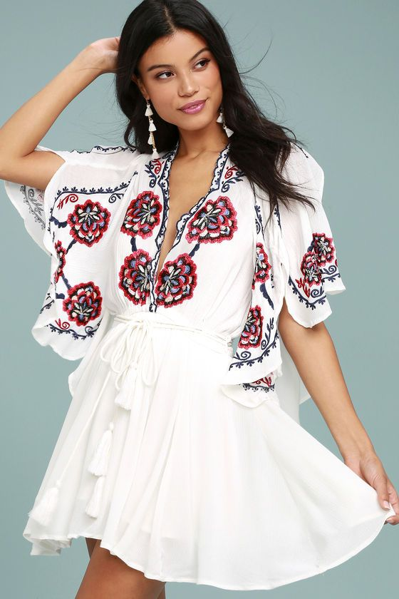 Take a walk on the wild side with the Free People Cora White Embroidered Dress! Intricate navy blue, red, and beige embroidery decorates this flirty woven dress with a scalloped, plunging neckline and wide, fluttering sleeves with side slits. Elastic waistband, and an tasseled, wrap belt tops a leg-baring mini skirt.