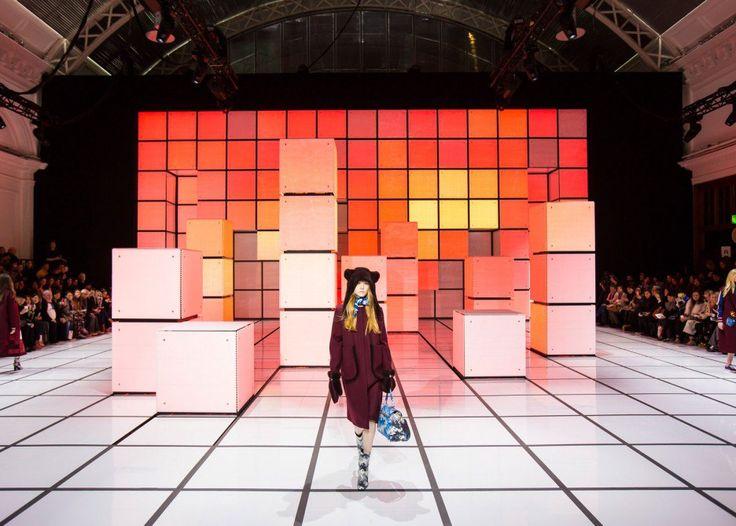 INCA Productions - авторы сцены для показа осенне-зимней коллекции Anya Hindmarch во время Недели Моды в Лондоне. Яркие, красочные поверхности - привет, 8-битная графика и кубик Рубика! Изначально сцена представляет собой пол и гигантскую стену из квадратных световых акриловых панелей, которые перемещаются и меняют цвет во время показа. Где-то в глубине подиума скрыты рельсы и лебёдки, которыми перемещаются кубы.