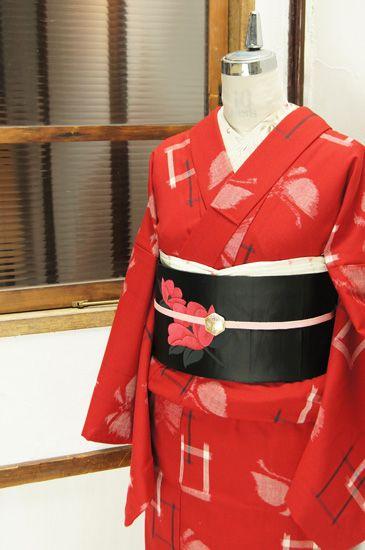 深みのある綺麗な赤色に重なりあう窓のような四角い絣模様と大きな蝶々が織り出されたウールの単着物です。