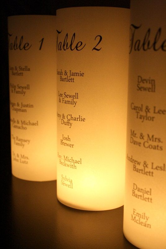 Seating Chart Luminarias from Etsy. ~~about $5.each/min 10 - probably could diy, its just the table # & names on vellum & placed inside glass cylinder (no bottom) with a votive or led.
