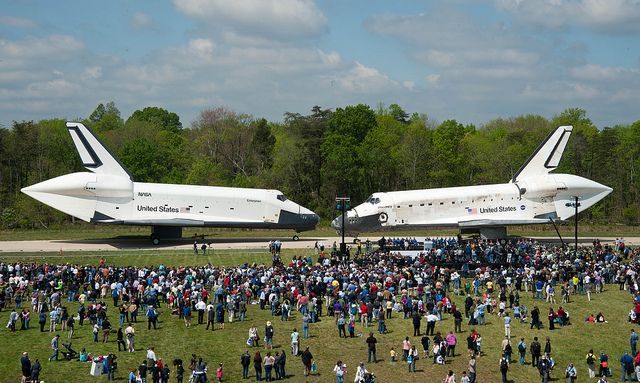 April 19, 2012. Space Shuttles Enterprise, left, and Discovery meet nose-to-nose at the beginning of a transfer ceremony at the Smithsonian's Steven F. Udvar-Hazy Center in Chantilly, Va. Space shuttle Discovery, the first orbiter retired from NASA's shuttle fleet, completed 39 missions, spent 365 days in space, orbited the Earth 5,830 times, and traveled 148,221,675 miles will now begin its new mission to educate and inspire. Photo Credit: (NASA/Smithsonian Institution/Carolyn Russo)