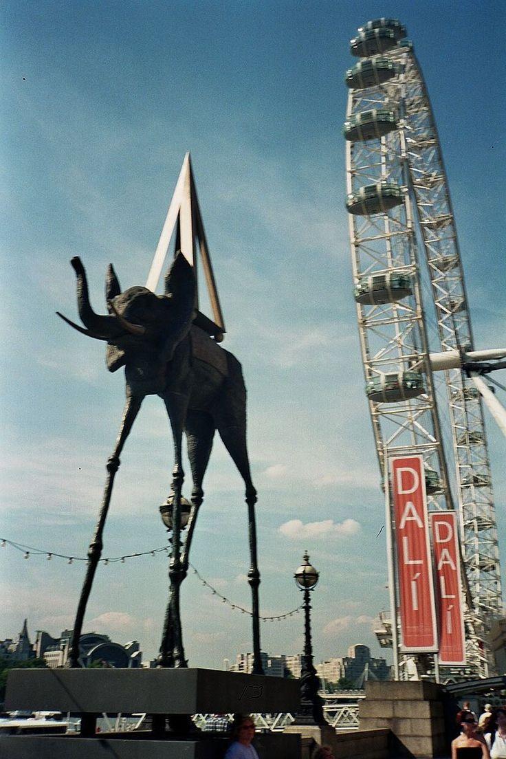 London Dali Exhibition - Salvador Dalí -  Exposición sobre Dalí en Londres. En primer término hay una escultura de un elefante de patas alargadas con una pirámide en el lomo, idéntico a uno de los que aparecen en el cuadro. Al fondo se encuentra el London Eye. Wikipedia, la enciclopedia libre