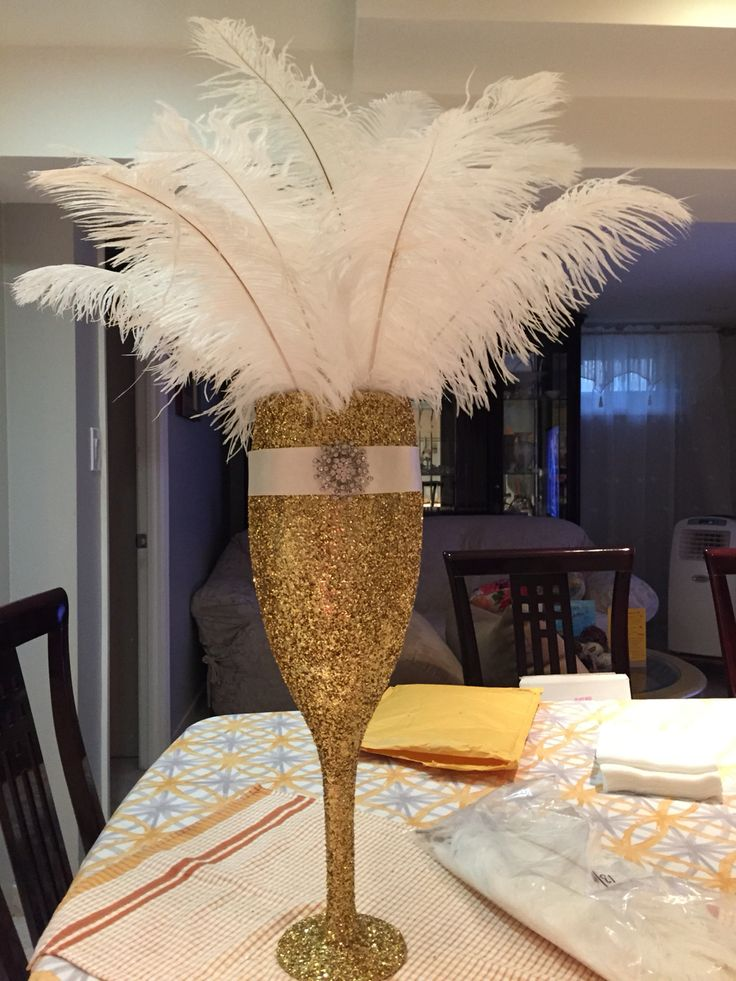 Large champagne glass from Michaels. Spray adhesive, gold glitter, wide satin ribbon, large crystal brooch. Filled with ostrich feathers as a centerpiece for a great Gatsby themed bridal shower.