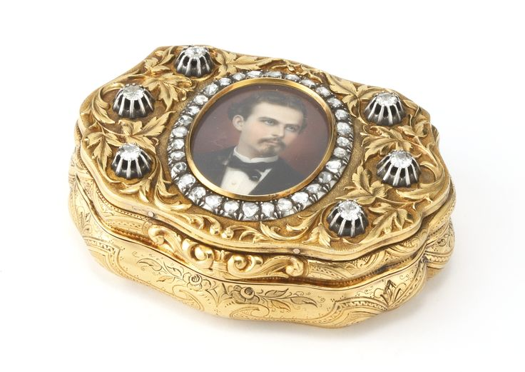 Royal: A German varicolor gold and diamond presentation snuff box of cartouche shape, cover mounted with a miniature of King Ludwig II in a border of rose diamonds and surrounded by six large old mine diamonds within chased foliage on matted ground, sides and base engraved with flowers and strapwork, interior with old German inscription dated 1881, from Ludwig II of Bavaria to Empress Elizabeth of Austria (Sisi), Charles Colins Söhne, Hanau, dated 1881. -Sotheby's