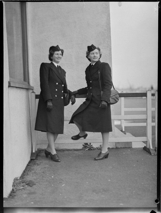 Portrait of Miss B P Morton and Miss L M Magnus, TEAL Stewardesses in uniform outside an unidentified building, Mechanic's Bay, Auckland. Date: 13 Aug 1946. Photograph taken by Whites Aviation.