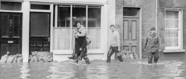 Sandbags provide little protection from the flooding in Campsie Road, Omagh and from this we can see too keep dry a lift is the order of the day.  22/11/1969