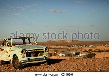 east german car wreck Trabant and the landscape around Coober Pedy, South Australia, Australia - Stock Photo