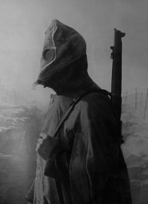 A soldier dons a primitive gas mask.