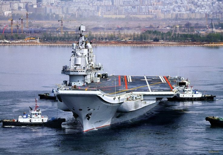 China's first aircraft carrier (refurbished Russian Varyag) Liaoning returning to port in Quingdao after training cruise.