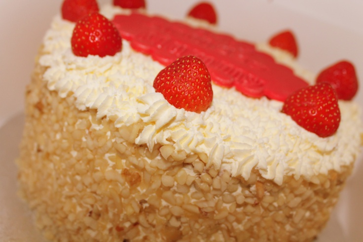 Retro cream cake layered with strawberry jam, double cream, fresh strawberries and covered with crushed nuts.