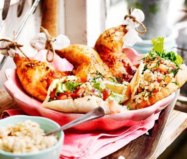 Ugnsstekt kycklingklubba i sällskap med pitabröd fyllt med sallad, kikärtsröra och tomatsallad.
