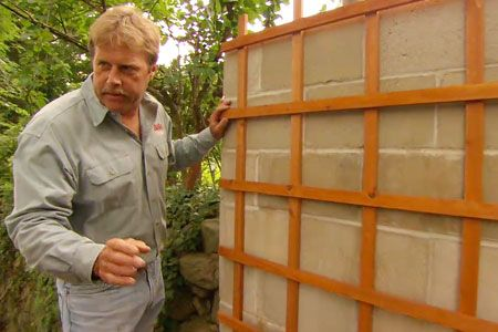 This Old House landscape contractor Roger Cook shows how to hide—and beautify—an ugly concrete-block retaining wall with a trellis.