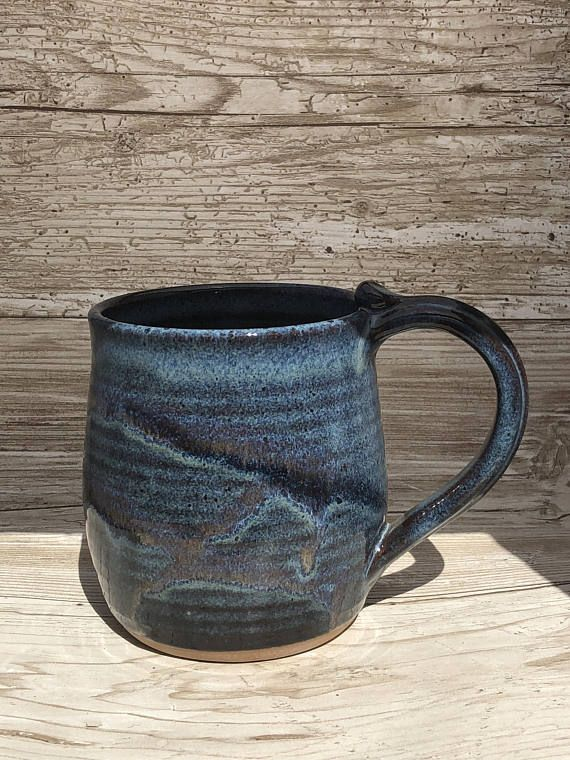 Stoneware Pottery Mug - This large handled mug holds 16 oz. with enough space left over for cream. A large comfortable handle makes this a nice mug for home or office. Keeps coffee hot. Mug is Ovenproof and Microwave and Dishwasher safe. Mug photographed is the exact item you will receive so there are no surprises. Approximate Dimensions: Lip of mug is approximately 3 1/2 diameter and is 4 3/4 tall. Color name: Fish Creek - The beautiful floating blue glaze is splashed with darker...