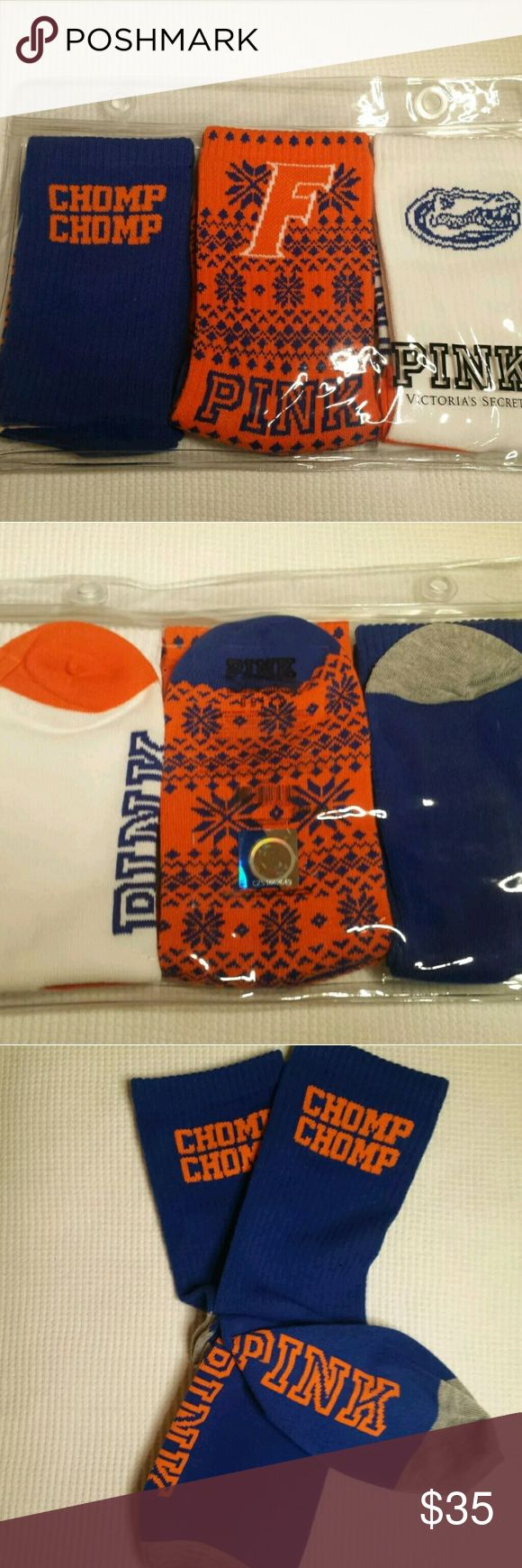 """PINK University of Florida UF Gators 3 Crew Socks 3 pair of BRAND NEW UF GATOR crew socks are in the original factory packaging in clear reusable seal-able pouch. The orange socks has the Florida """"F"""" symbol in orange with a blue holiday """"sweater"""" pattern all over & PINK logo on the bottom of the orange pair. The white pair has the Gator head logo in blue at the top of the socks & PINK logo in blue on the bottom. Blue pair has """" CHOMP CHOMP"""" in orange at the top & PINK logo in blue on the…"""