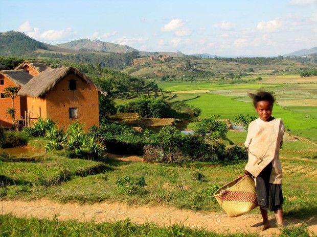 Cette petite fille se tient devant un paysage typique du Betsileo, dans les hauts plateaux de Madagascar.