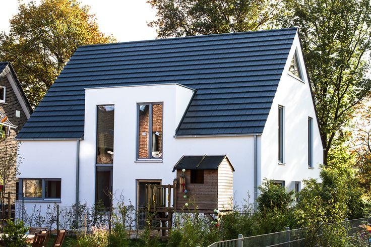 Außenansicht von KfW-40 Haus fertig: 2mm Putz in Sto weiß, Lärchenholzfenster in Ral 7040