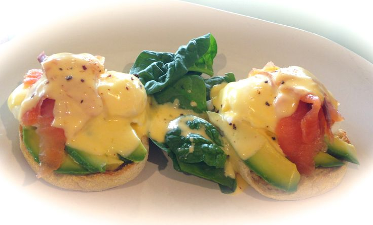 Poached eggs, smoked salmon, avocado, baby spinach, hollandaise sauce, served on an english muffin for breakfast.