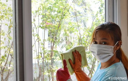 Cute Asian woman with mask & rubber gloves cleaning