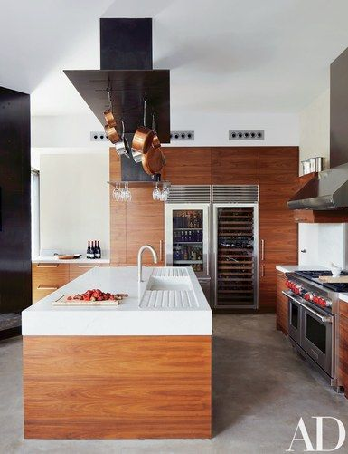 The pot rack and marble-top island in the #kitchen were custom made, the refrigerator and wine storage are by Sub-Zero, and the range and hood are by Wolf | archdigest.com