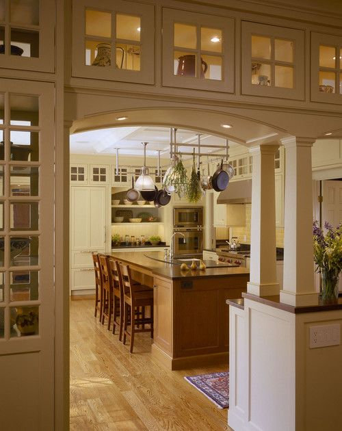 This is an example of a classic kitchen with arched entryway and display cabinets. It was remodeled with beaded inset cabinets, white cabinets, and white backsplash. Modern pot racks provide more additional storage and improves the kitchen aesthetic. The kitchen island also contains natural wood cabinets and paired with three wood chairs. Photo by Battle Associates, Architects - Discover traditional kitchen design ideas
