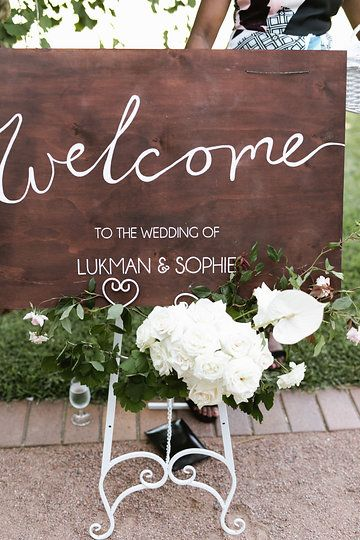 Wooden welcome sign and floral arrangement