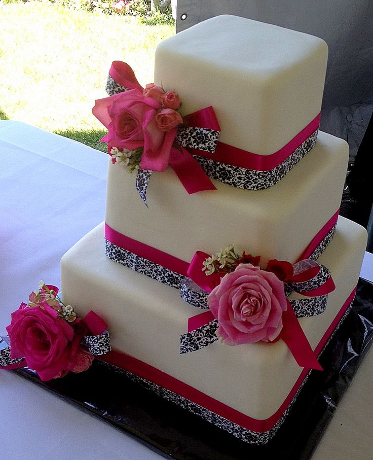 Hot Pink and Damask Wedding Cake - Sometimes the simplest details can be the sweetest - two ribbons made into bow to surround flowers - sets off the contemporary edge of this wedding cake- the colors continue inside with alternating layers of red velvet with cream cheese buttercream and strawberries and champagne - YUM