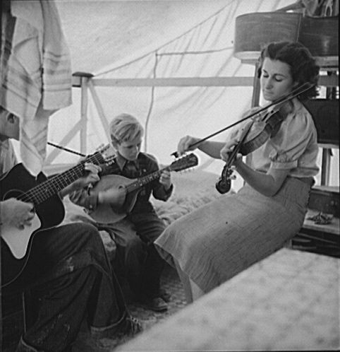 Migrant family from Arkansas playing hillbilly songs at a Farm Security Administration emergency migratory camp in Calipatria, California. This 1939 photo was taken by Dorothea Lange who was traveling the country under the commission of the Farm Security Administration. Her photographs helped humanize the struggle of American families during the Great Depression.