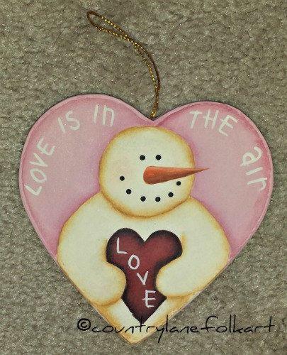 En este corazón de papel maché, he pintado un muñeco de nieve para el día de San Valentín. Perfecto para un árbol estacional, para colgar en tu ventana, o para adjuntar a un regalo para un especial de una persona.  El corazón mide 4 x 3 3/4 pulgadas, aproximadamente. Se adjunta un cable de oro para colgar.  Listado es para el adorno de corazón de color rosa solamente.  Si usted quisiera comprar el adorno de corazón púrpura, haga click aquí…