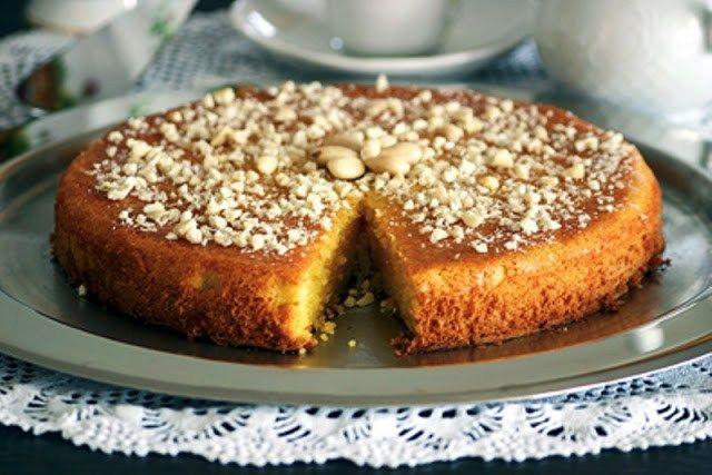 Ένα ζουμερό και πεντανόστιμο κέικ που αρέσει πολύ σε μικρούς και μεγάλους.    Υλικά    100γρ. αλεύρι μαλακό    100γρ. πούδρα αμυγδάλου    255γρ. ζάχαρη    75γρ. βούτυρο αγελάδος, λιωμένο    4 αβγά    4γρ. μπέικιν πάουντερ    110γρ. κρέμα γάλακτος    1 λοβό βανίλιας    1½γρ. αλάτι    100γρ. αμύγδαλα καβουρδισμένα, χοντροσπασμένα    ζάχαρη άχνη για το σερβίρισμα    Εκτέλεση    Προθερμαίνετε