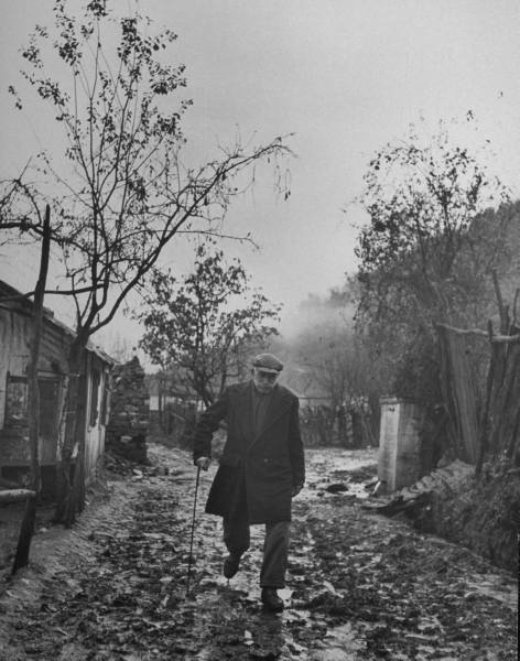 Civil War/Greece Lt. Col. Georgios Economitas using his cane to help him walk home.Location:Louzesti, Greece Date taken:December 1947 Photographer:John Phillips