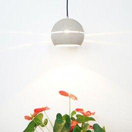 Betonleuchte aus rohem Beton mit Lightbeam. Diverse Farbvarianten sind durch Pigmentierungen möglich. Die Lampe ist eine abgestufte, fast geschlossene Kugel. Das Licht tritt durch die untere Öffnung heraus. Der Betonkörper wird von einem umlaufenden Plexiglasring unterbrochen durch den das Licht nach außen scheint. In dem Textilkabel befindet sich ein Stahlseil, welches das Gewicht der Lampe sichert. An der Fassung befindet sich eine Zugentlastung. Die Lampe wird mit einer goldenen…