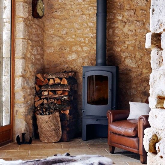 Wood burner looks great against exposed brick wall. The leather chair and reindeer hide make this a cosy snug