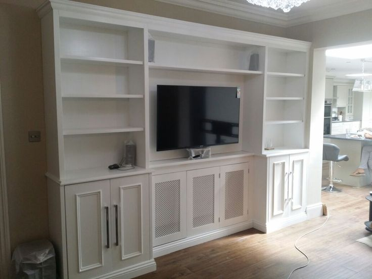 Traditional cabinets with a central radiator cover and bookcases for family room shelves makeover