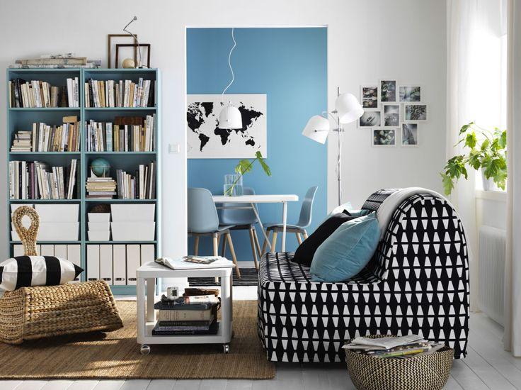 """Ein kleines Wohnzimmer, u. a. eingerichtet mit LYCKSELE LÖVÅS 2er-Bettsofa mit Bezug """"Ebbarp"""" in Schwarz/Weiß, einem weißen Couchtisch auf Rollen und einem Schaukelstuhl aus Bananenstaudenfasern"""