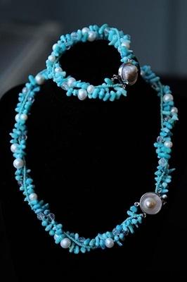 Setul este realizat din coral nuantat turcoaz, perle albe, margele de nisip turcoaz si bile transparente fatetate. Este compus din colier si bratara si ambele piese au inchizatori deosebite-cate o perle prinsa in sidef. Setul se poarta rasucit.