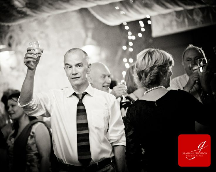 Male wedding guest raising a glass to the happy couple following the speeches at a wedding www.grahamcrichton.com