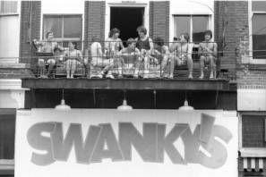 Group on balcony over Swanky's bar on Court Street near Ohio University campus, 1981 :: Ohio University Archives