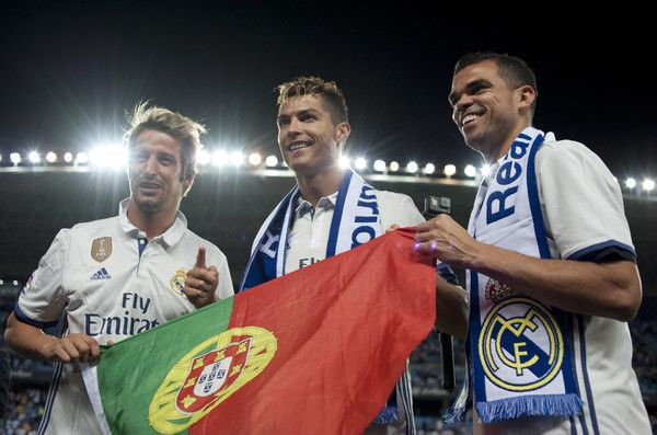 Real Madrid Portuguese players Fabio Coentrao, Cristiano Ronaldo and Pepe pose with a Portuguese flag as they celebrate at the end of the Spanish league football match Malaga CF vs Real Madrid at La Rosaleda stadium in Malaga on May 21, 2017..Real Madrid won their 33rd La Liga title and first for five years as Cristiano Ronaldo's 40th goal of the season helped seal a 2-0 win at Malaga today... / AFP PHOTO / SERGIO CAMACHO