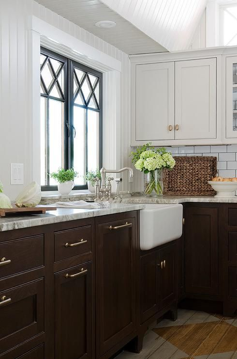 Gorgeous kitchen features light grey upper cabinets and dark brown lower cabinets paired with gray ...
