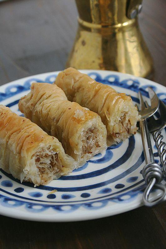 Baklawa rolls Ingrédients : 18 à 20 feuilles Filo 250 g de noix concassées et en poudre (mélangées) 250 g de beurre  Pour le sirop : 400 ml d'eau 300 g de sucre 2 pelures (zeste) de citron jaune 1 c; à café de jus de citron