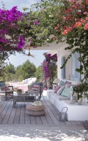 Outdoor living with overhanging, colorful flowers and abundant plant life-outdoor living room.