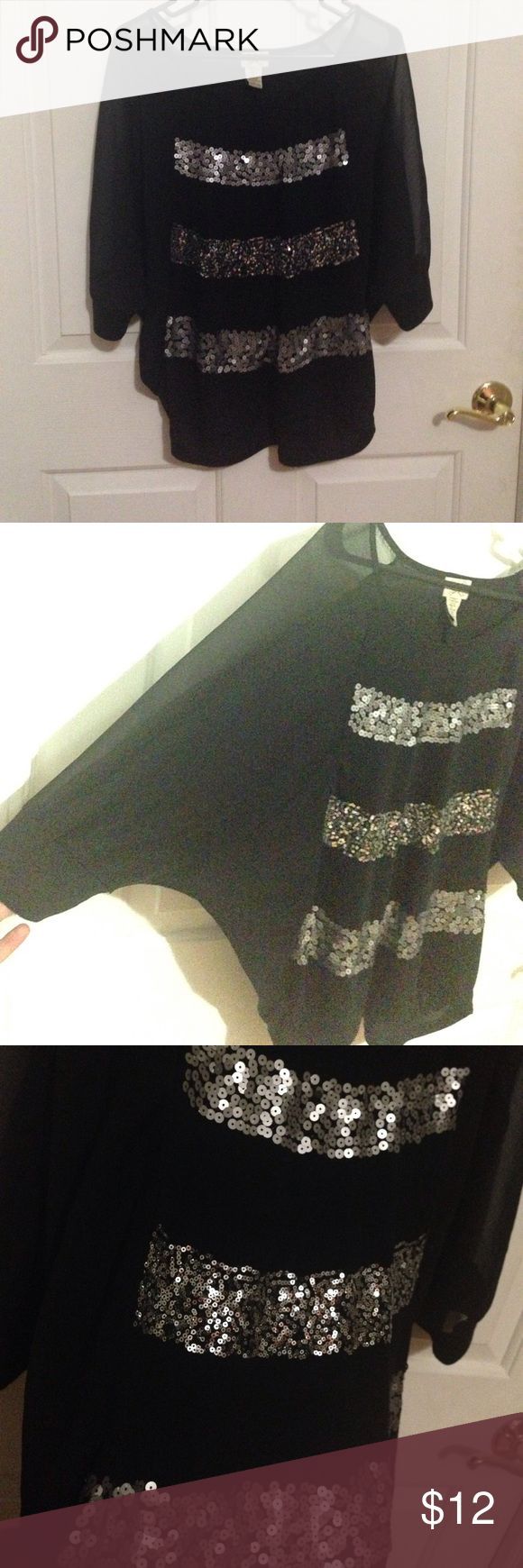 Black sequin blouse Black knit (front and back) blouse with thick bands of silver sequins across front. Two bands are matte silver and the center band is glossy/shiny silver. The arms are 3/4 length and are sheer except for the cuff which is the same knit material as rest of shirt. Sleeves are batwing style as shown in 2nd photo. Tops Blouses