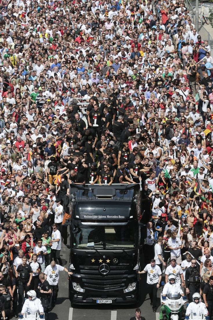 Thousands of Germany fans line the streets as the national football team makes its way to Berlin's landmark Brandenburg Gate to celebrate winning the World Cup
