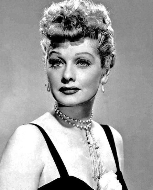 1950 - Lucy Ball wears an elaborate curly roll fringe bang.